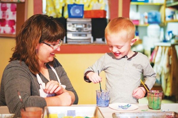 Jenni Petersen-Brant paints with a young student.