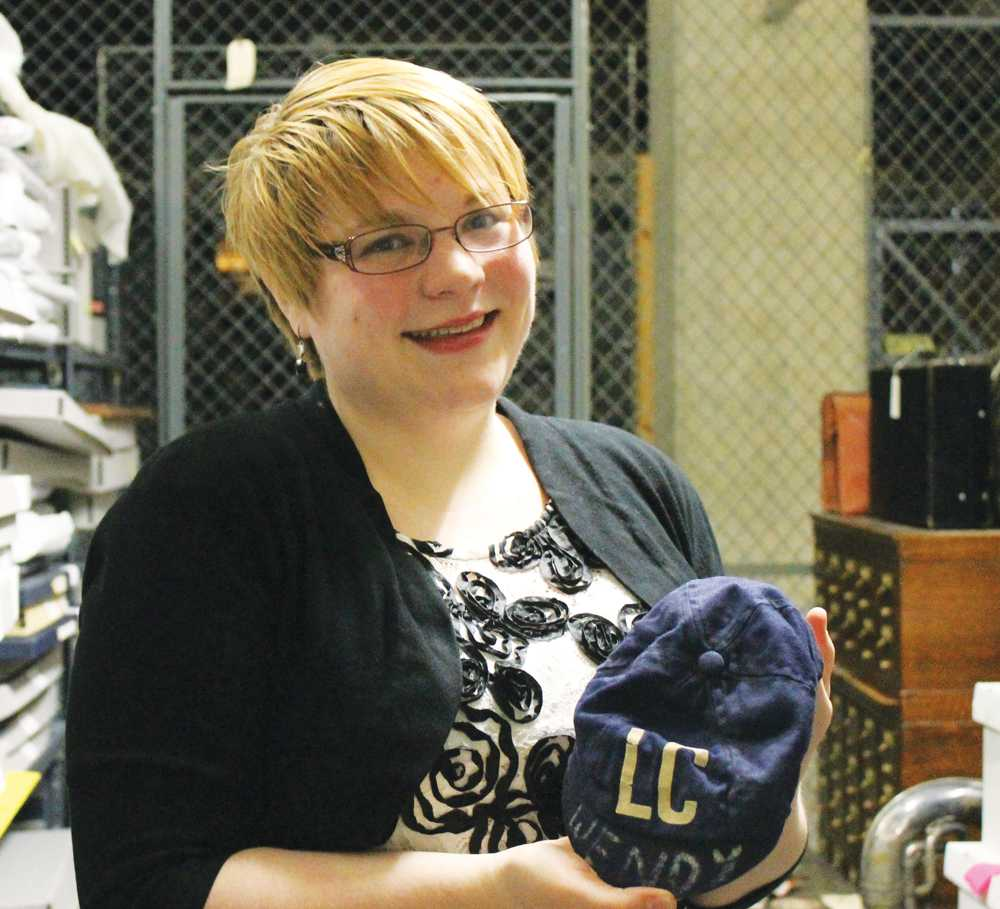 College Archivist Hayley Jackson with a archived Luther College baseball hat.