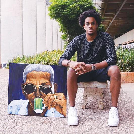 Muha Bazila poses with one of his portraits.