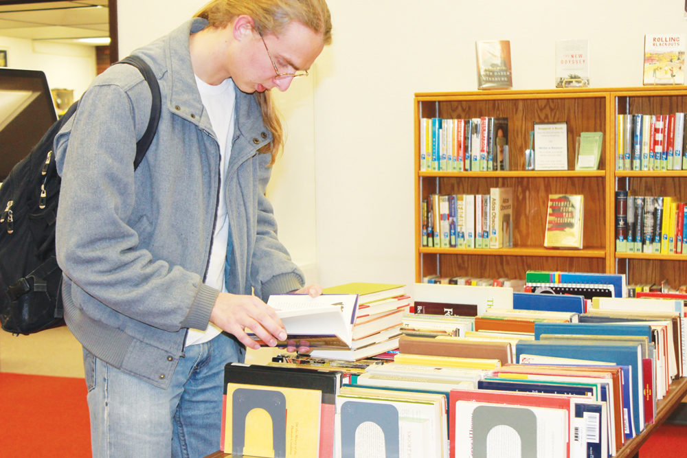 Jedidiah Nixon ('17) flips through a book at the the book sale.