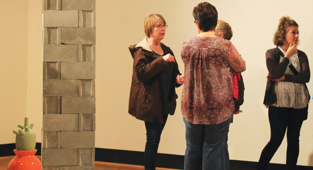 Community member's discuss Luke Severson's gallery near the cinder block wall piece.