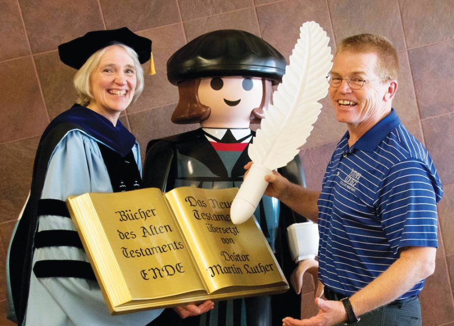 Luther+College+President+Paula+Carlson+and+Campus+Pastor+Mike+Blair+help+out+the+life-sized%2C+Playmobil+Martin+Luther.+Students+were+encouraged+to+take+a+picture+with+the+life-sized+Martin+and+Carlson+in+the+Union+on+March+28.