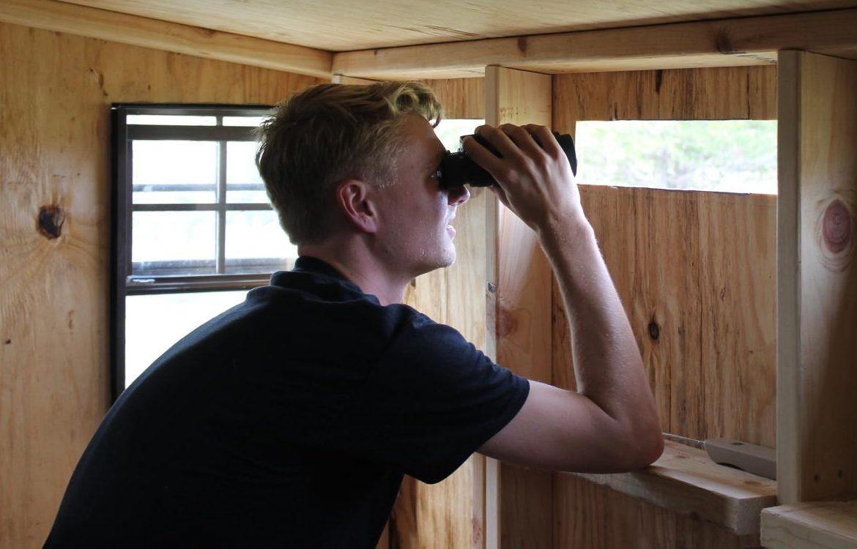 Luther student intern Matt Lagus ('19) watches raptors from the bird blind.