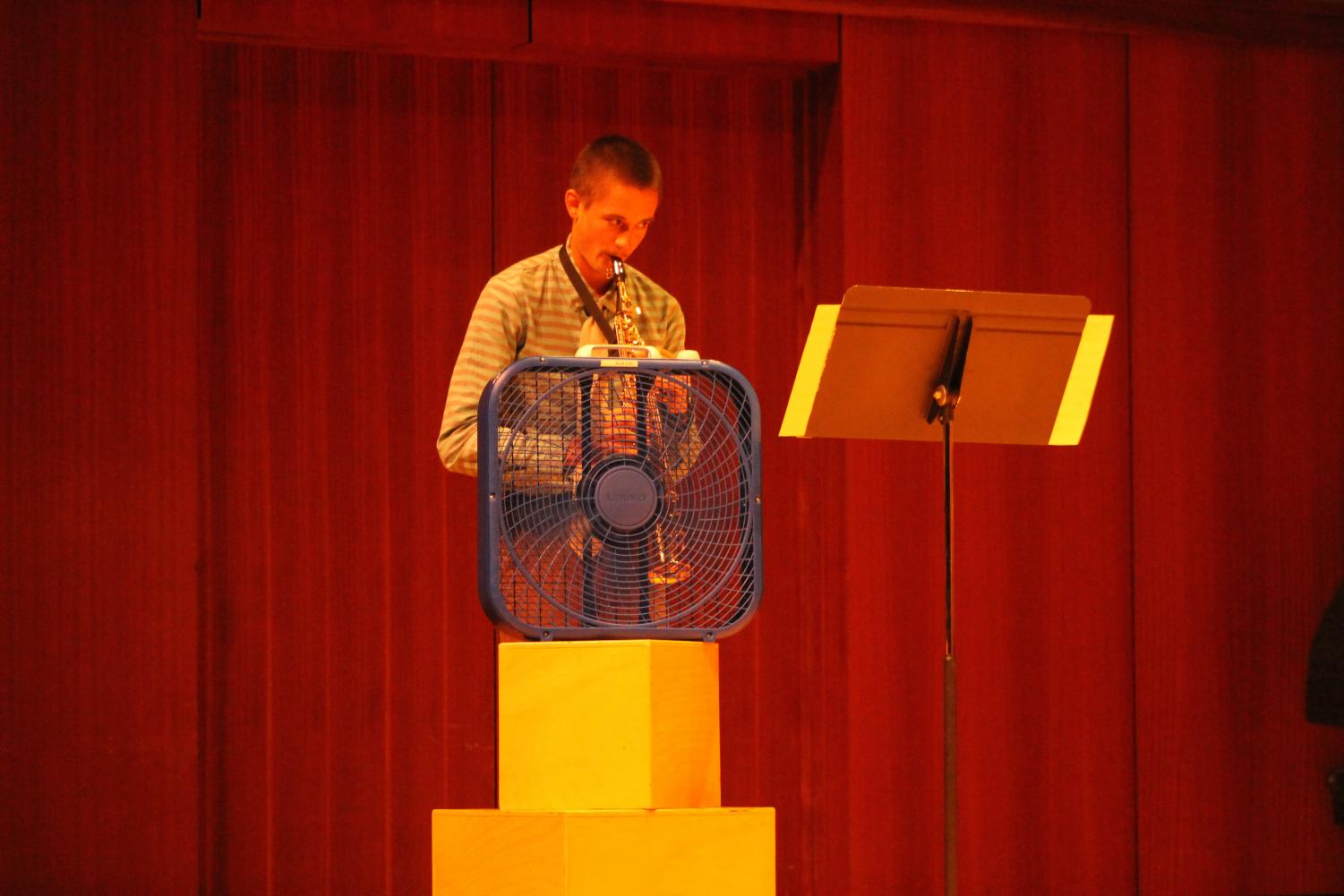Hunter Prueger ('18) plays his soprano saxophone into a box fan for his composition recital.