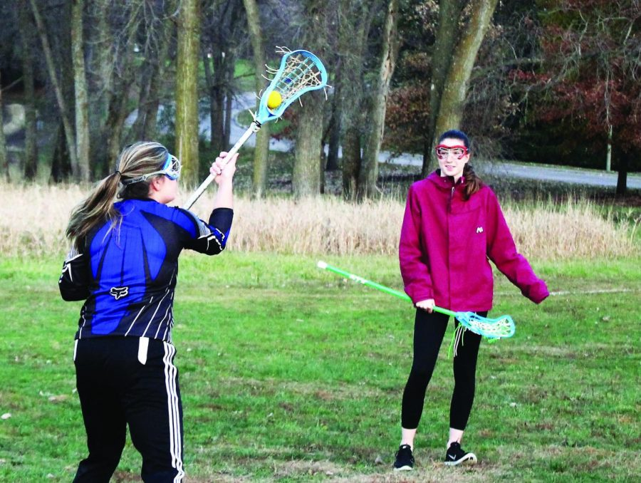 Fallon+Cassidy+%28%E2%80%9819%29+and+Frances+Rhodes+%28%E2%80%9820%29+practice+lacrosse+skills+by+Lindeman+Pond.