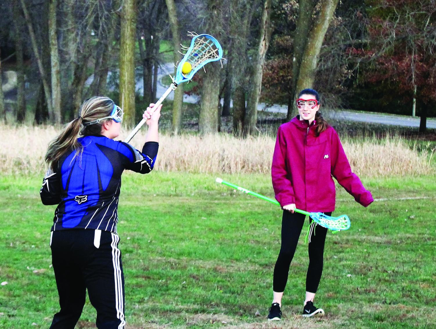 Fallon Cassidy ('19) and Frances Rhodes ('20) practice lacrosse skills by Lindeman Pond.