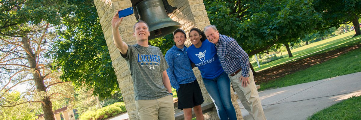 Luther Ambassadors Grant Preheim ('18), Sam Poppen ('18), and Harleigh Boldridge ('18) pose with Cross Country Assistant Coach Kirk Neubauer.