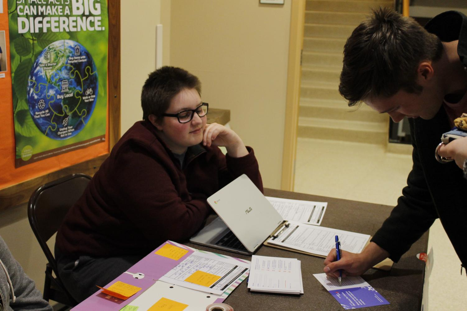 Conner Kujak ('21) responds to a survey as Susie Wold ('20) tables for voter registration.