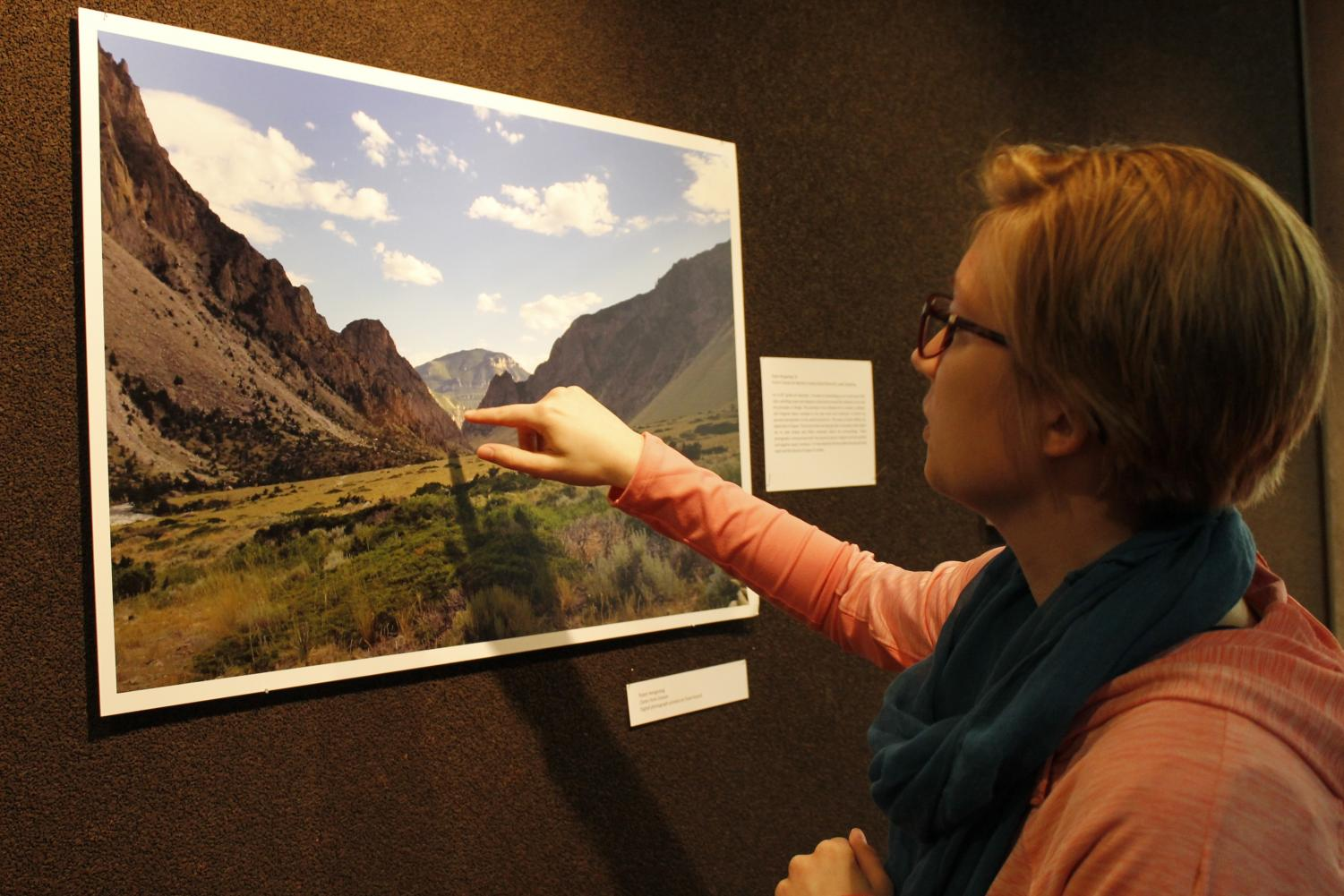 "Steffenee Voigt ('18) locates the focal point of Robin Schone Hengesteg's ('16) ""Clarks Fork Canyon"" on display in  Preus Library."