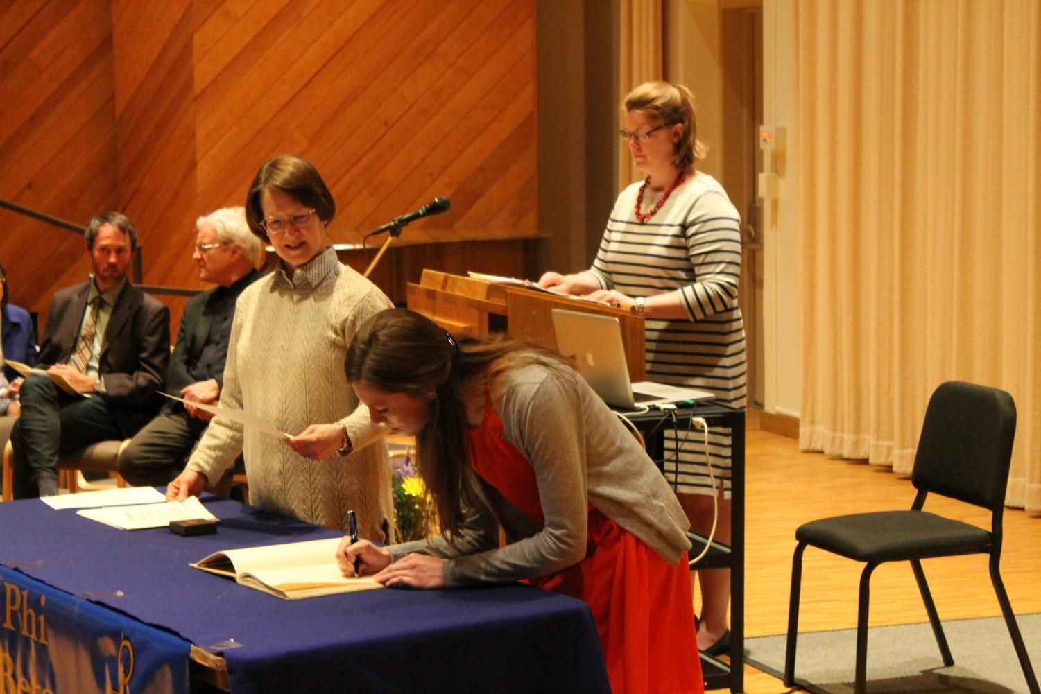 Devin Hedlund ('18) signs her induction into Phi Beta Kappa.