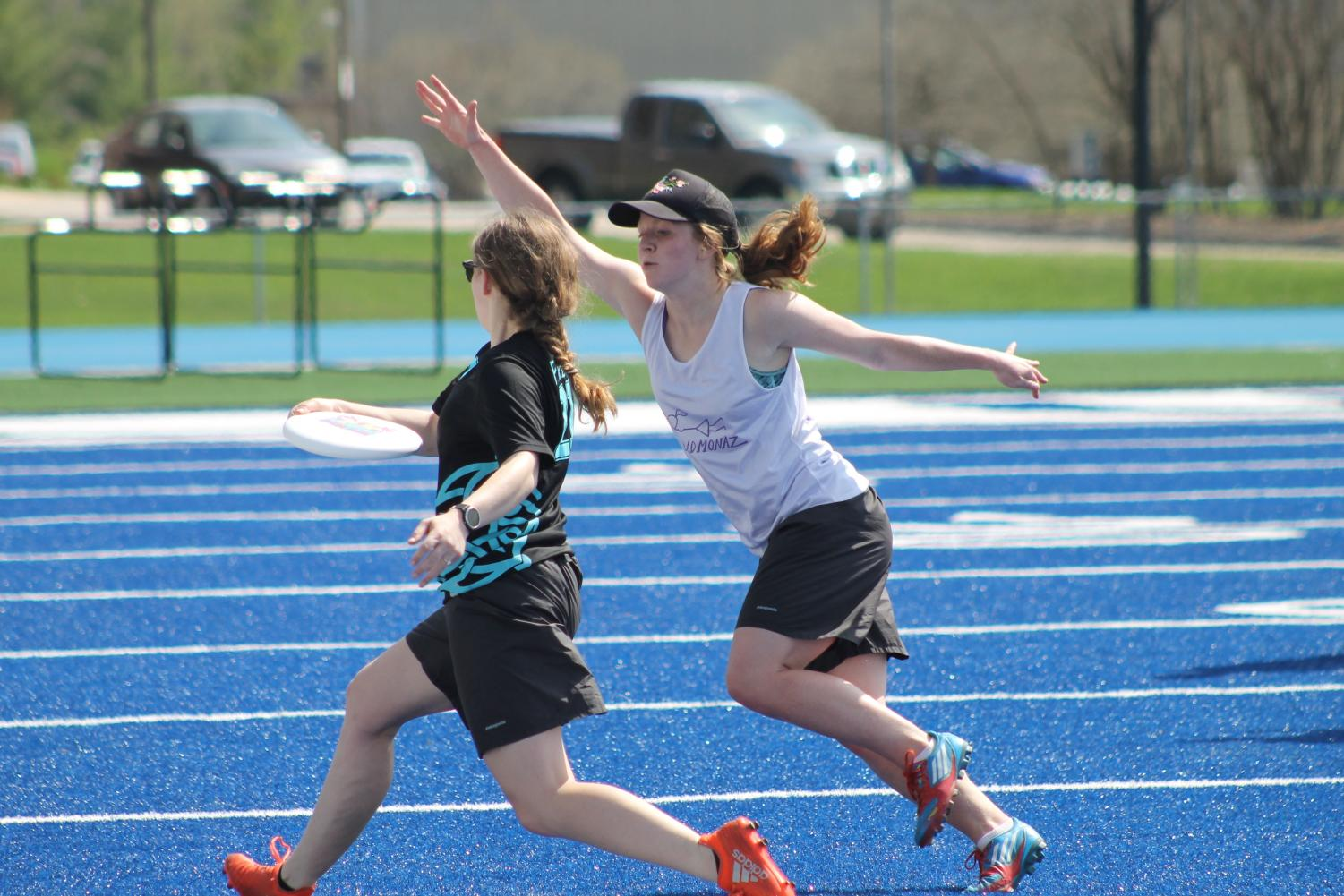 Cora Egherman ('19) attemps to throw a frisbee as Alexis Hove ('18) defends.