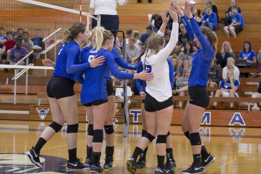 Luther volleyball players celebrate after scoring  a  point  against College of  St.  Benedict  on  Saturday,  Sept. 22.
