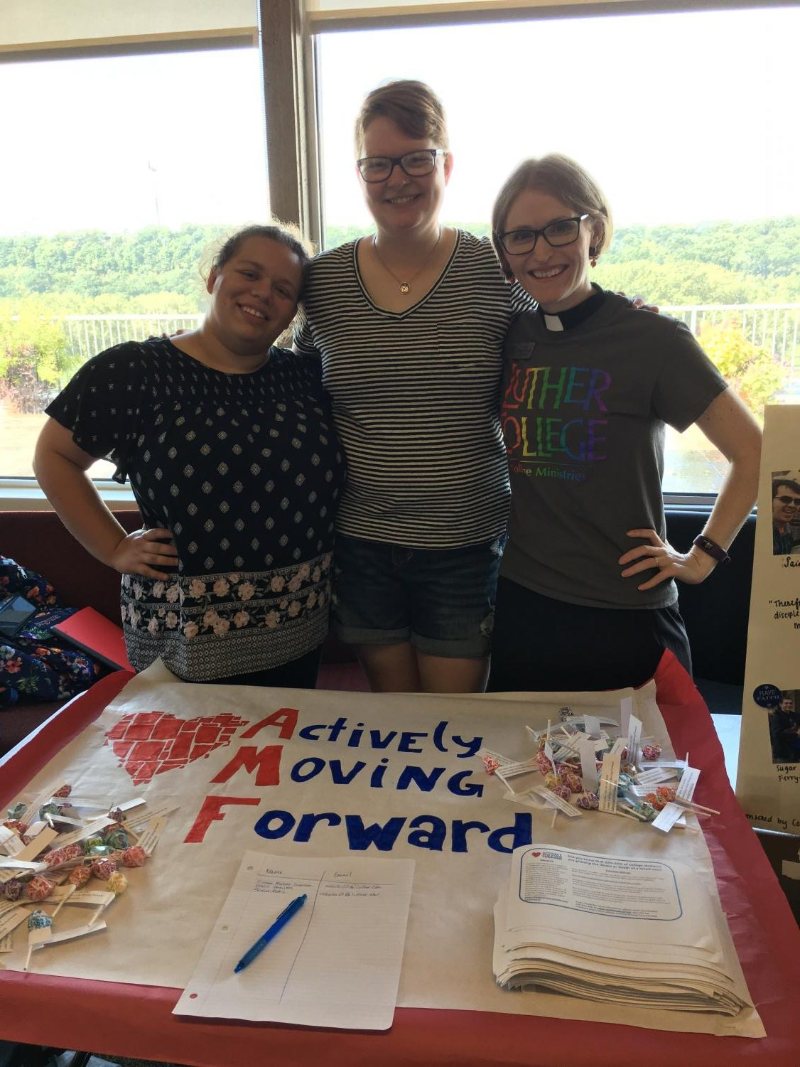 Alex Atal ('19), Jana Mueller ('19), Pastor Annie Edison-Albright advertising Actively Moving Forward at the Fall Activities Fair