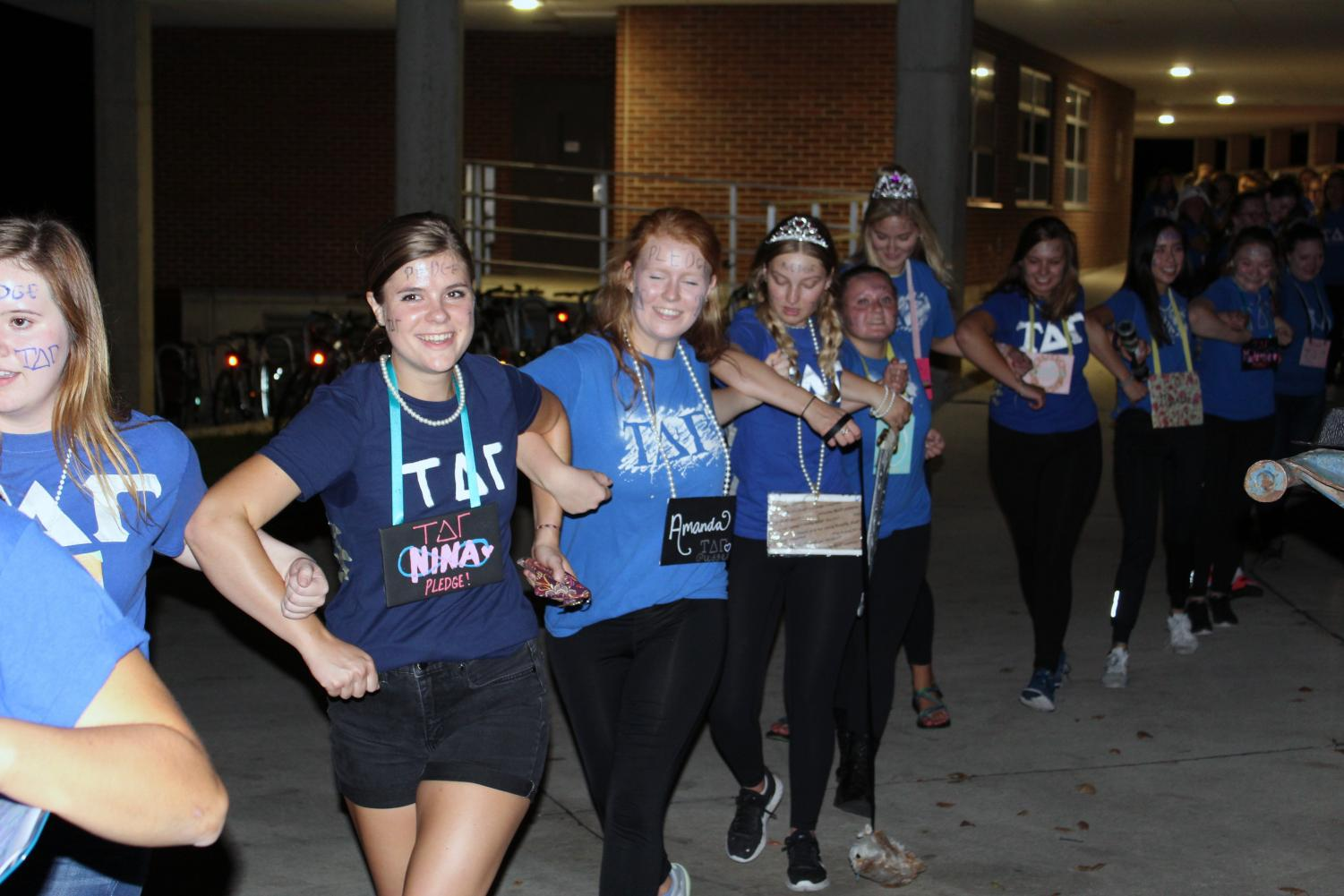 Nina Johnson ('19) and Amanda Nyquist ('19) hook elbows and walk around campus with other pledges on pick up night in 2017.