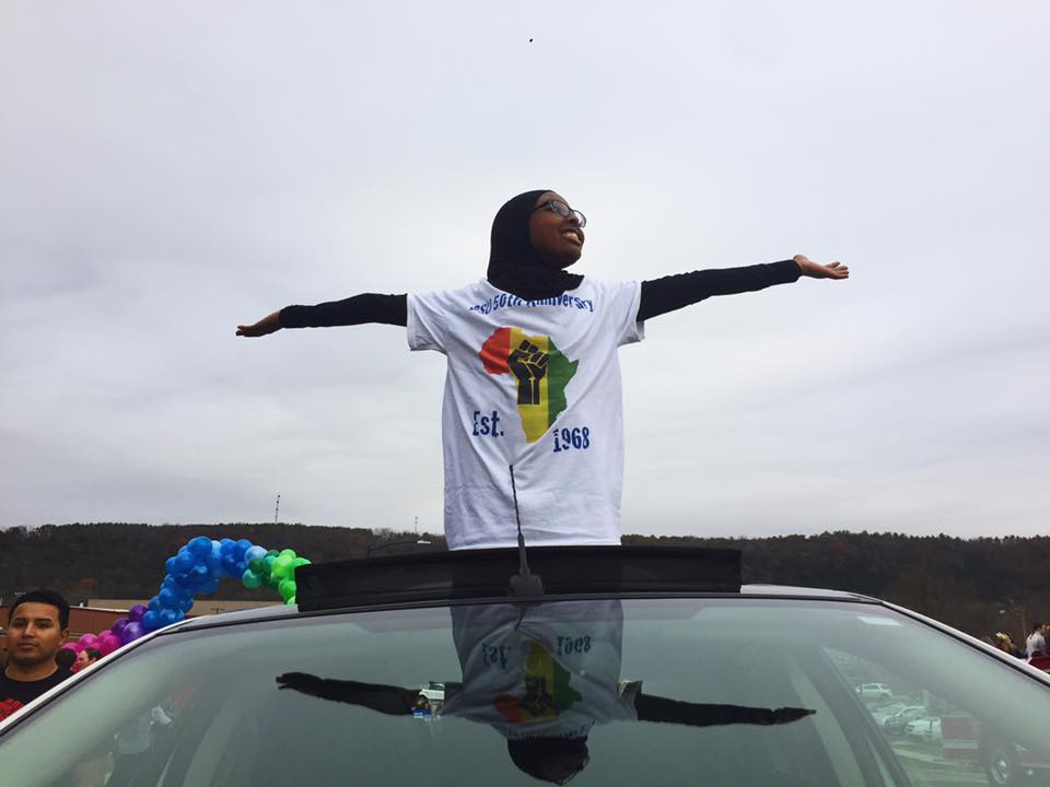 Asha Aden ('20) poses on the BSU car driven in the homecoming parade.