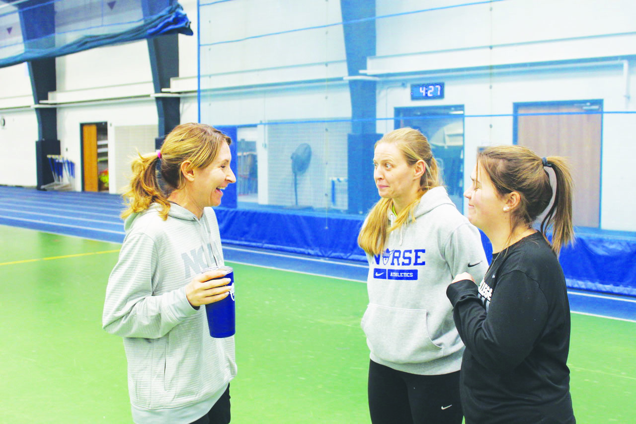 Renae Hartl, Teri Olson ('05), and Kristen Winter ('15) chat at practice.