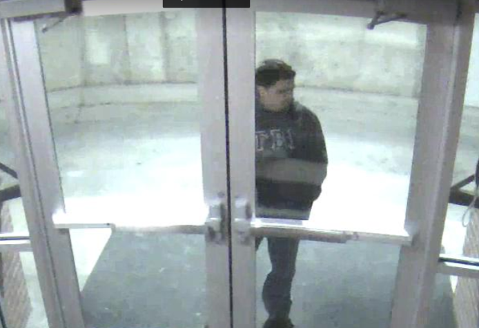 A security camera at Miller Hall captures the suspect trying to enter the dorm.
