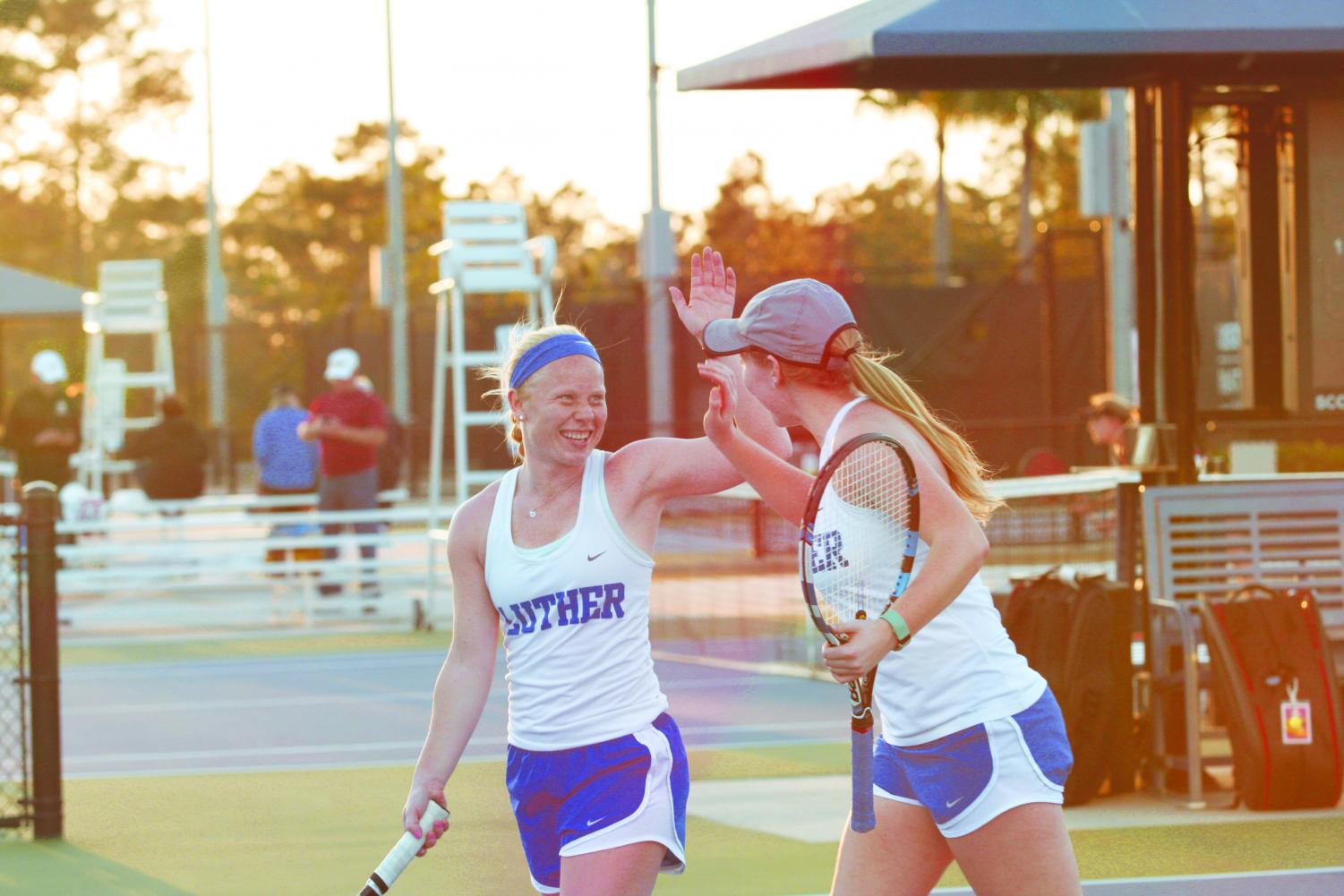 Ellie Hemker ('20) and Megan Grimm ('22) high-five on the United States Tennis Assocation National Campus courts during games over spring break.