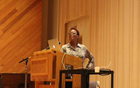 """Deborah Smith Pollard sings along to """"Oh Happy Day"""" during her lecture."""