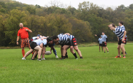 Luther players and alumni engage in a three man scrum.