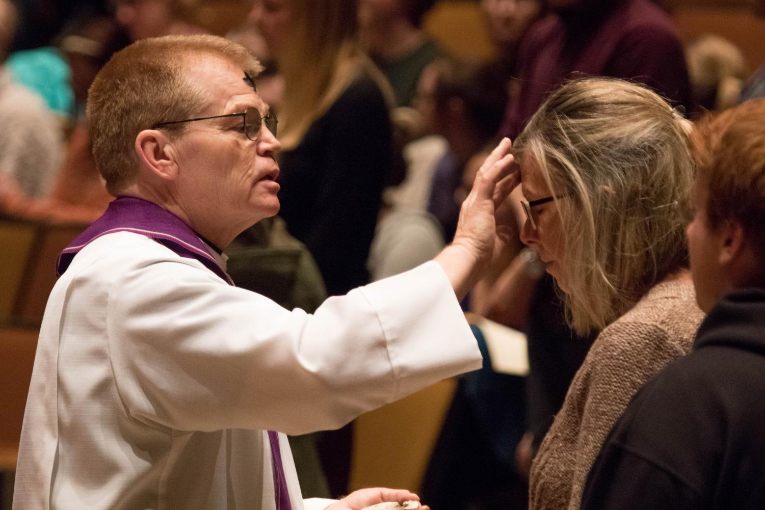 College Pastor Mike Blair places ashes on parishioners' foreheads on Ash Wednesday in 2018.