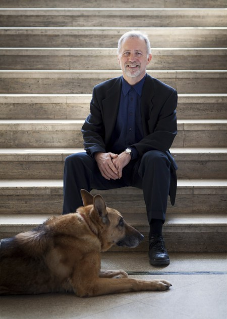 Leif E. Vaage poses with his German Shepard in a faculty photo for Emmanuel College of Victoria University in the University of Toronto.