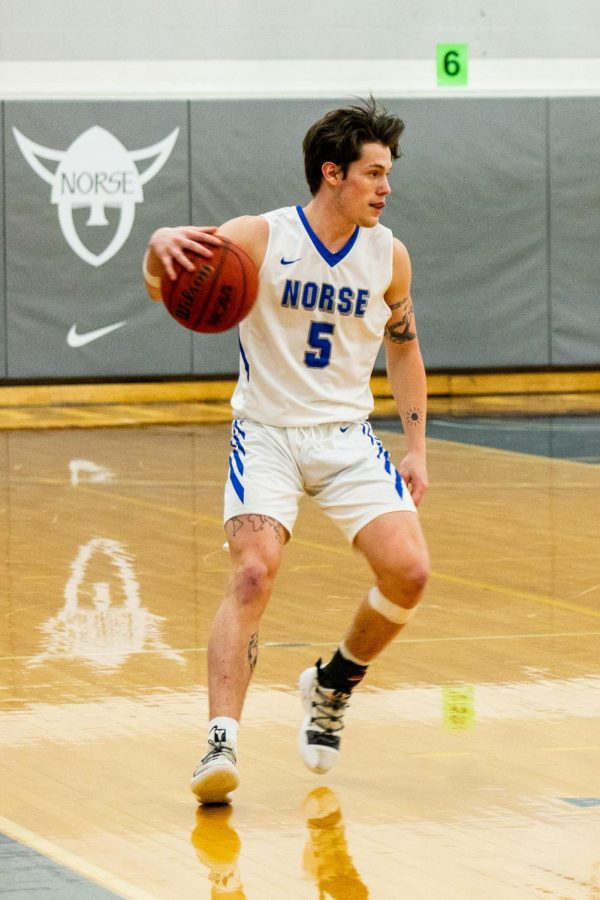 Gage Thompson ('21) dribbles the basketball during a game against Central College on February 10.