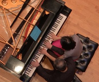 Professors Du Huang (left) and Xiao Hu (right) perform duet on the same piano. Photo Courtesy of Mick Layden.