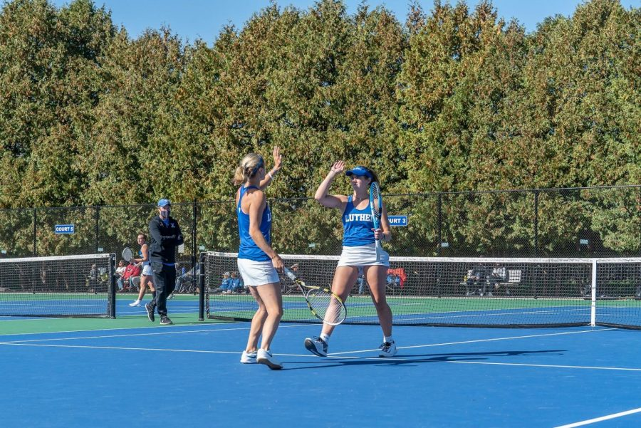Devon Bourget ('21), left, and Shelby Cook ('22), right, celebrate winning a point in their doubles match during a meet against Central College on October 4, 2020.