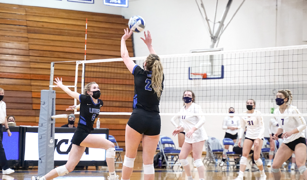 Callahan ('21), right, sets middle blocker Rachael Luebbe ('22), left, during a game against Loras on March 3, 2021.
